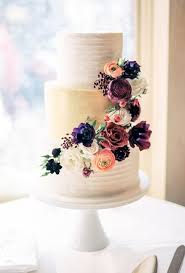 A Three Tiered White Wedding Cake Adorned With Flourish Of Deeply Hued