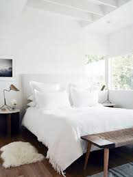 White Bedroom Featuring A Canvas Headboard Linens Wooden And Twine Bench Bronze Lighting