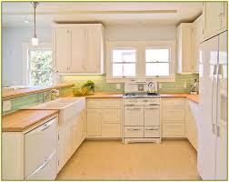 green subway tile backsplash with kitchen cabinet and laminate