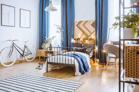 blaue vorhänge und fahrrad im gemütlichen schlafzimmer mit pflanzen auf schrank neben einem bett mit lichtern