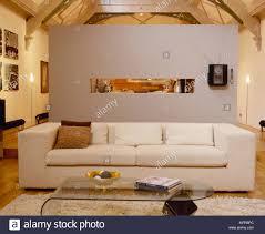 wohnzimmer mit sofa couchtisch aus glas trennwand und