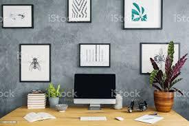 einfache plakate hängen grau rohe wand innen studie ecke wohnzimmer mit schreibtisch aus holz mit mockup monitor frische pflanzen und bücher stockfoto