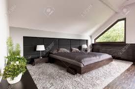 helle und geräumige schlafzimmer mit einem großen japanischen bett polster wand teppich und dekorative bonsai bäumen