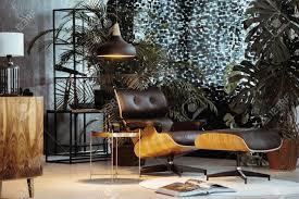 kleines dunkles wohnzimmer mit vintage möbeln und exotisch aussehenden pflanzen