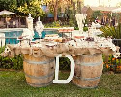 Rustic Burlap Wedding Decorations With Glass Cake Jars And Small Flowers On Long Wooden Table
