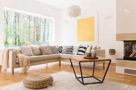 couchtisch aus holz und weißes sofa im gemütlichen trendigen wohnzimmer