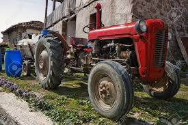 Old Farm Tractor With A Wooden Trailer In Village Stock Photo