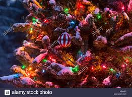 Christmas Ornament And Lights Hanging On A Snow Covered Tree Outside At Night