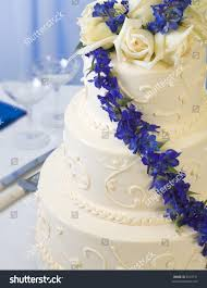 Traditional Decorated Wedding Cake With Blue Delphiniums And Champagne Glasses