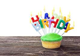 colorful happy birthday cupcake with candles on white background