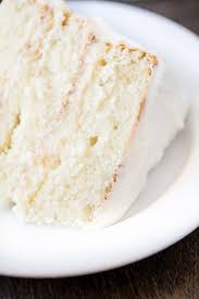 Closeup of a slice of the most amazing white cake on a white plate on a