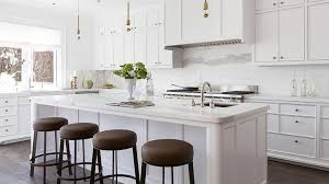 white kitchen island with brown leather barstools and half