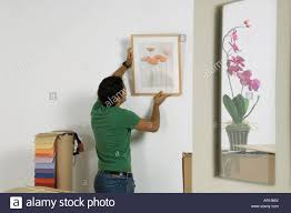 Young Man Hanging A Painting