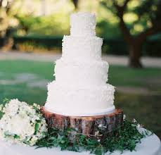 White Wedding Cake On Top Of Wood Tree Trunk Slab