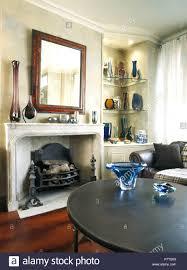 blaues glas vase auf schwarzen kaffee tisch vor einem kamin