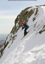 An Image Of Dylan Dropping Into A Steep Line On His Skis In The Cliff Trail
