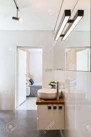 moderne hochglanz weiß badezimmer mit dekorativer beleuchtung spiegel und arbeitsplatte mit waschbecken offene türen im hintergrund