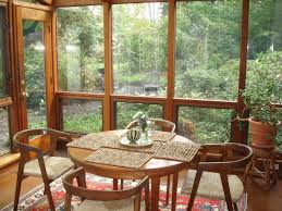 A Set Of Wood Chairs And Round Table In Rustic Sunroom Small Rattan Console