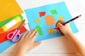 Child Keeps A Pencil In Hand And Draws Scissors Glue Stick Colorful Paper