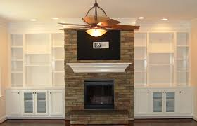 classic white oak wood bookshelves with stone fireplace of