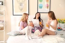 drei junge mädchen trinken saft und reden auf einem bett im wohnzimmer