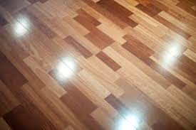 Polished Shiny Floor Made From Short Laminated Planks Reflecting The Light Four Overhead Spots