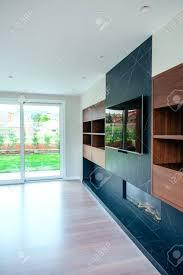 großes wohnzimmer leer mit kamin und tv