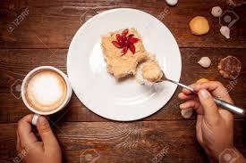 mittagessen im café nicht erkennbare person kuchen essen und kaffee zu trinken die tasse cappuccino und kuchen und plätzchen auf einem hölzernen