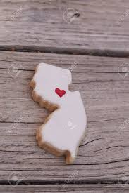 California Shaped Sugar Cookie With White Icing And A Red Heart On Rustic Wood Table