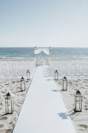 The Wedding Ceremony Space Was Decorated With White Chairs A Fabric Arch
