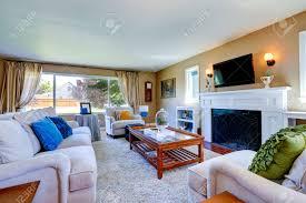 weicher beige wohnzimmer mit weißen möbeln glasplatte tisch kamin und fernseher