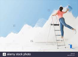 Woman On Ladder Painting Wall With Paint Roller