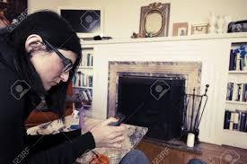 ein erwachsener kaukasischen frau in ihren frühen 30er jahren mit ihrem smartphone während der sitzung am wohnzimmer vintage färbung angewendet