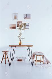 bank mit decke und schemel bei tisch mit orange vase gegen weiße wand mit galerie im esszimmer