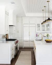 all white kitchen with brass accents black pendant lights