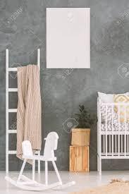baby schlafzimmer mit weißem kinderbett und schaukelpferd