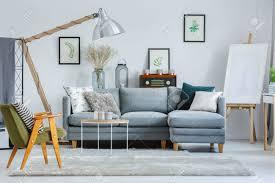 klassischer grüner sessel im wohnzimmer mit staffelei und designerle über grauem sofa mit kissen