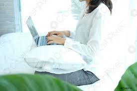 foto auf lager asiatische frau mit computer laptop auf dem bett im schlafzimmer arbeiten aus der ferne zu hause freizeit lebensstil