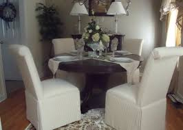 Round Pedestal Table Surrounded By Scroll Back Parsons Chairs With Kick Pleat Skirts