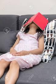 asiatische chinesische kleine mädchen auf dem sofa mit buch im wohnzimmer liegen