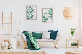 pflanze auf holztisch im neutralen wohnzimmer mit grünen kissen auf beige sofa und gemälden an der wand