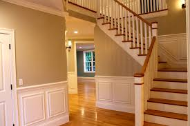 decorating hallway staircase with wood handrail and wainscoting