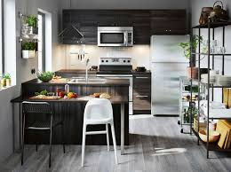 A Small Kitchen With Black Wood Effect Drawers Doors And Open Storage Space For