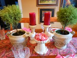 Indoor Green Plant In Rustic Pot With Red Candle And Ethnical Table Runner