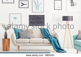 blaue decke auf beige sofa zwischen hölzernen stuhl und