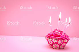 Birthday Pink Cupcake with Four Candles and Pink background royalty free stock photo