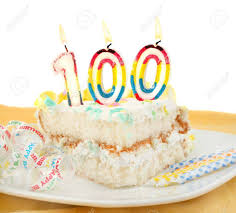 Slice of frosted festive birthday cake with candles and ribbon celebrating 100 year old birthday or