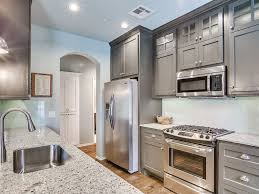 small galley kitchen with gray cabinets andino white granite and
