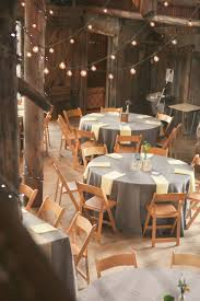 Rustic Country Wedding Reception Decorations With String Lamps And Round Tables Also Wooden Folding Chairs