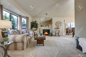 Light Filled Family Room With Vaulted Ceiling Above Beige Gray..